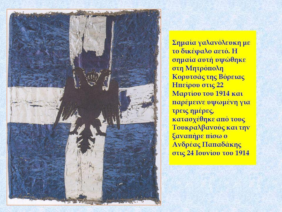 Σημαία γαλανόλευκη με το δικέφαλο αετό. Η σημαία αυτή υψώθηκε στη Μητρόπολη Κορυτσάς της Βόρειας Ηπείρου στις 22 Μαρτίου του 1914 και παρέμεινε υψωμέν