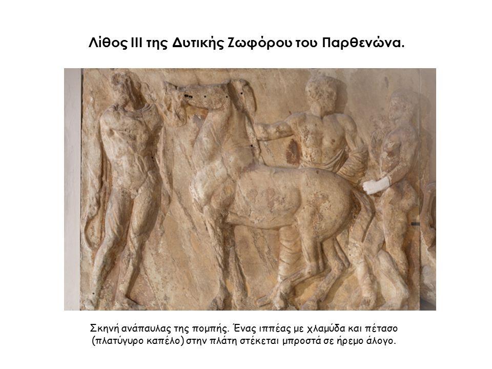 Σκηνή ανάπαυλας της πομπής. Ένας ιππέας με χλαμύδα και πέτασο (πλατύγυρο καπέλο) στην πλάτη στέκεται μπροστά σε ήρεμο άλογο. Λίθος III της Δυτικής Ζωφ