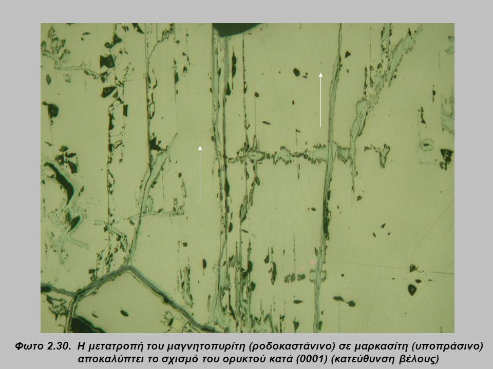 Φωτο 2.30. Η μετατροπή του μαγνητοπυρίτη (ροδοκαστάνινο) σε μαρκασίτη (υποπράσινο) αποκαλύπτει το σχισμό του ορυκτού κατά (0001) (κατεύθυνση βέλους)