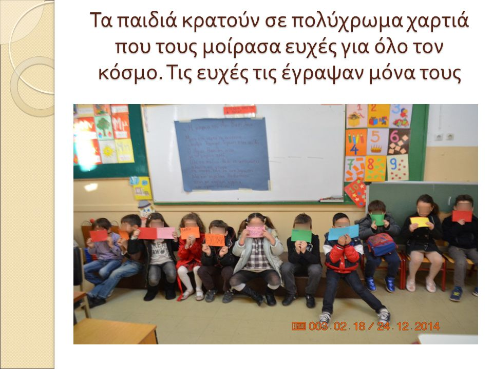 Τα παιδιά κρατούν σε πολύχρωμα χαρτιά που τους μοίρασα ευχές για όλο τον κόσμο.