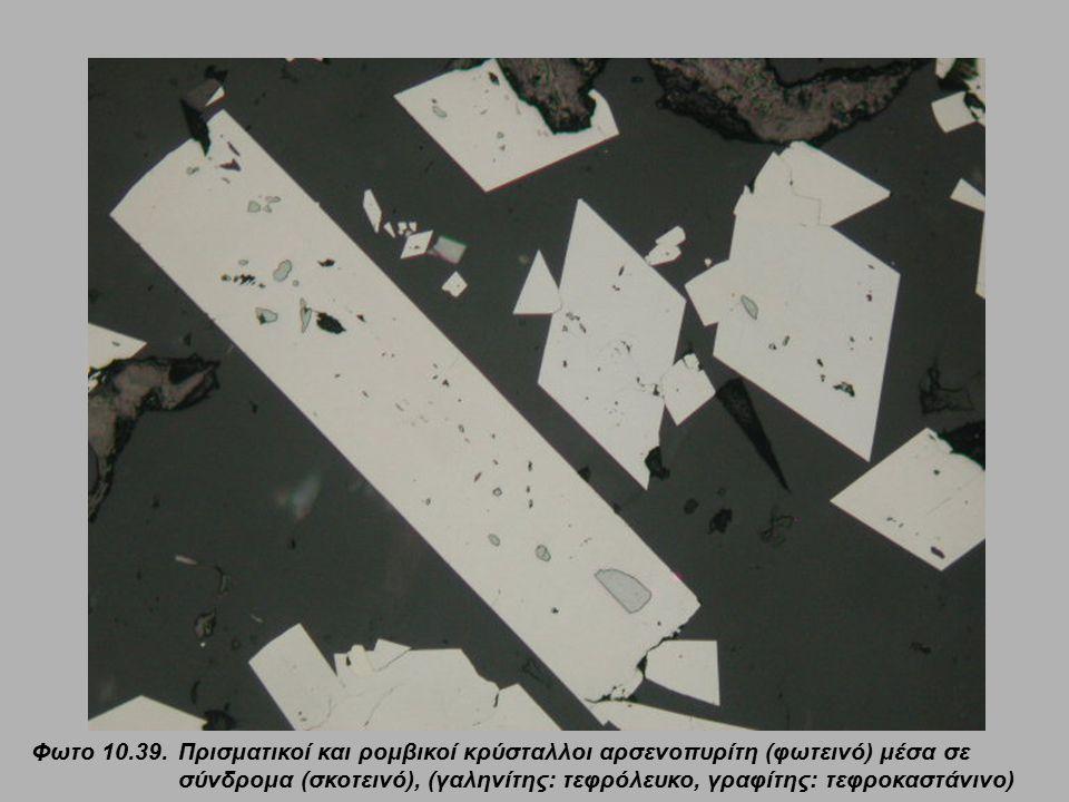 Φωτο 10.39. Πρισματικοί και ρομβικοί κρύσταλλοι αρσενοπυρίτη (φωτεινό) μέσα σε σύνδρομα (σκοτεινό), (γαληνίτης: τεφρόλευκο, γραφίτης: τεφροκαστάνινο)