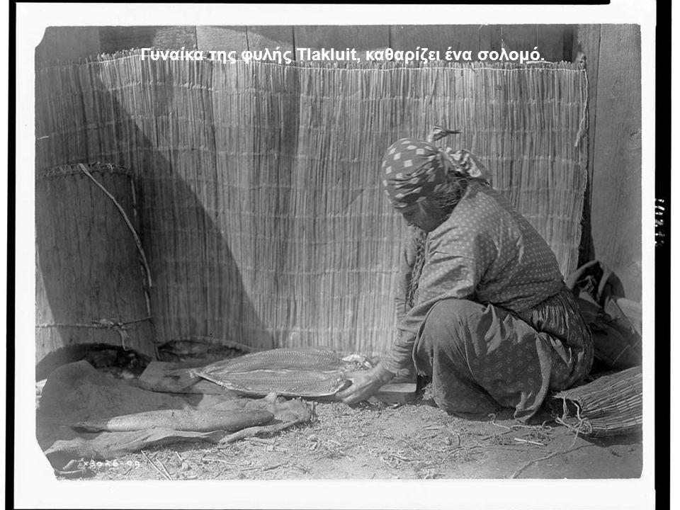 Γυναίκα της φυλής Tlakluit, καθαρίζει ένα σολομό.