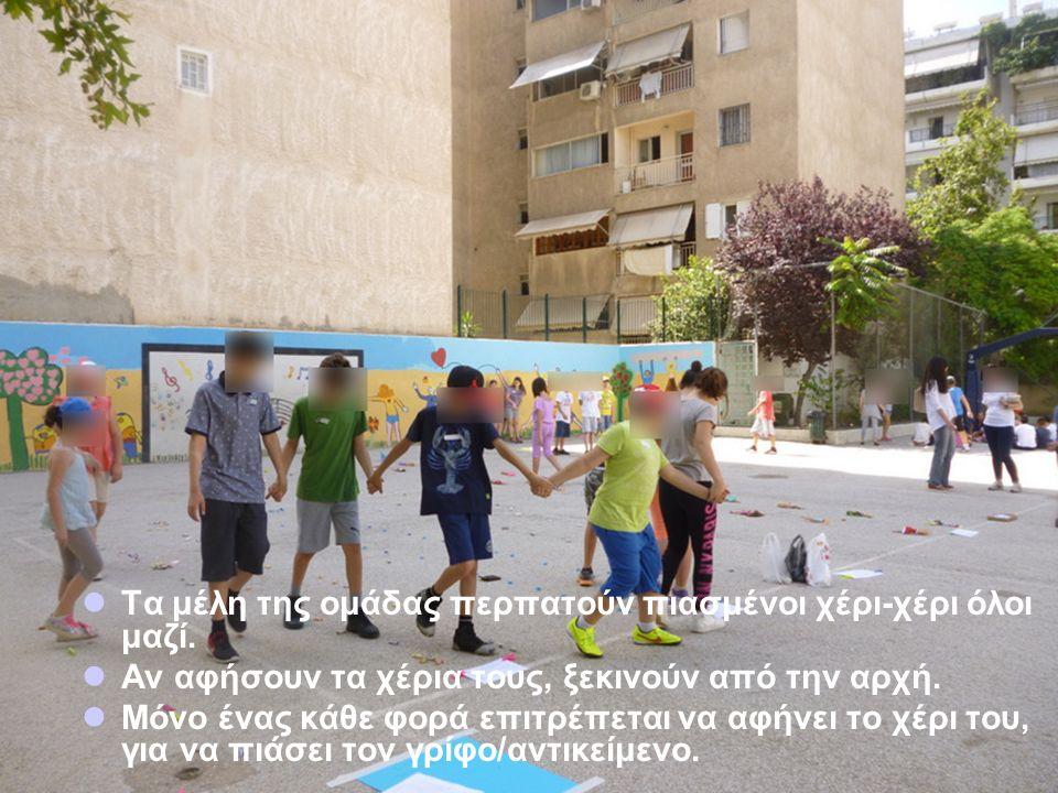 Τα μέλη της ομάδας περπατούν πιασμένοι χέρι-χέρι όλοι μαζί.