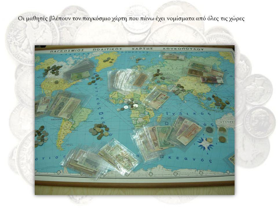 Οι μαθητές βλέπουν τον παγκόσμιο χάρτη που πάνω έχει νομίσματα από όλες τις χώρες