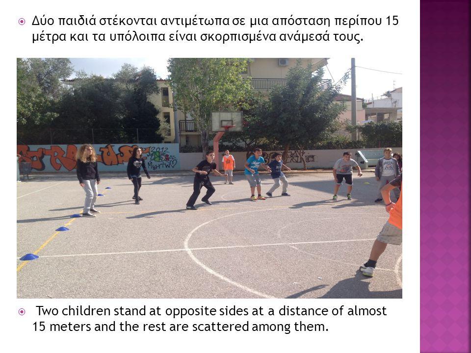  Δύο παιδιά στέκονται αντιμέτωπα σε μια απόσταση περίπου 15 μέτρα και τα υπόλοιπα είναι σκορπισμένα ανάμεσά τους.  Two children stand at opposite si