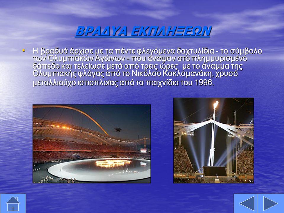 ΒΡΑΔΥΑ ΕΚΠΛΗΞΕΩΝ •Η•Η•Η•Η βραδυά άρχισε με τα πέντε φλεγόμενα δαχτυλίδια - το σύμβολο των Ολυμπιακών Αγώνων - που άναψαν στο πλημμυρισμένο δάπεδο και