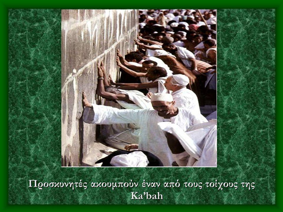 Προσκυνητές ακουμπούν έναν από τους τοίχους της Ka'bah