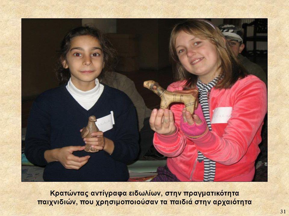 31 Κρατώντας αντίγραφα ειδωλίων, στην πραγματικότητα παιχνιδιών, που χρησιμοποιούσαν τα παιδιά στην αρχαιότητα